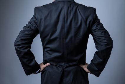 スーツを着ているビジネスマン、腰に手を当てる