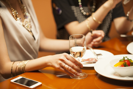 Women are eating while drinking white wine in the restaurant