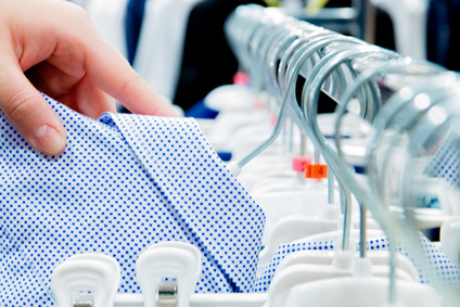 buyer's hands hang blue baby shirt on hanger in store