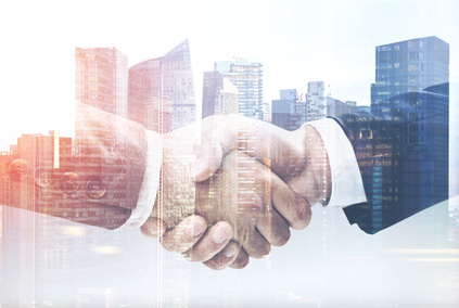 Two businessmen shake hands in a city close up