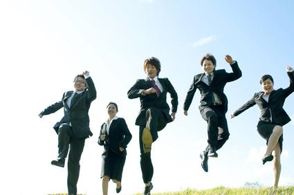 草原でジャンプをするビジネスマンとビジネスウーマン