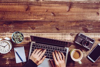 ウッドテーブルに並べたノートパソコンとコーヒー 小物雑貨