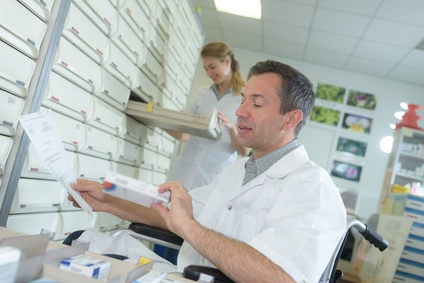 disabled male pharmacist choosing storing medicines
