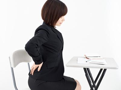 白背景で腰痛に悩む女性OL