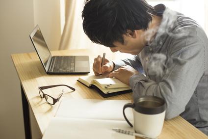 机の上で仕事・勉強をする男性