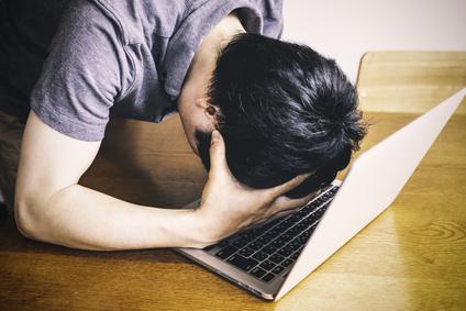 ノートパソコンの前で落ち込む男性